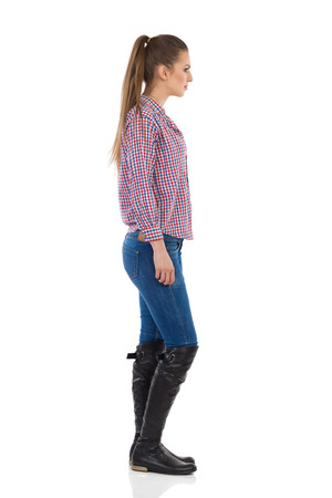 Photo for Young woman standing in jeans, black boots and lumberjack shirt. Side view. Full length studio shot isolated on white. - Royalty Free Image