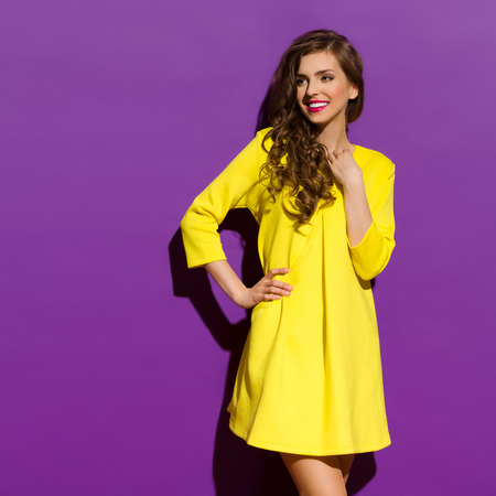 Photo for Beautiful smiling girl in yellow mini dress posing with hand on hip. Three quarter length studio shot on violet background. - Royalty Free Image