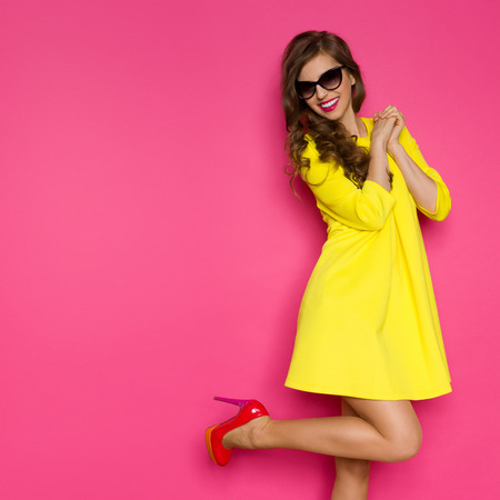 Foto de Excited girl in yellow mini dress posing on one leg against pink background. Three quarter length studio shot. - Imagen libre de derechos