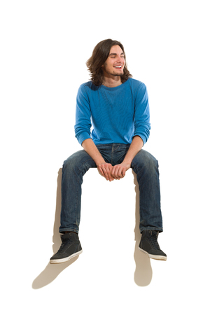 Photo pour Young man sitting on a banner, smiling and looking away. Full length studio shot isolated on white. - image libre de droit