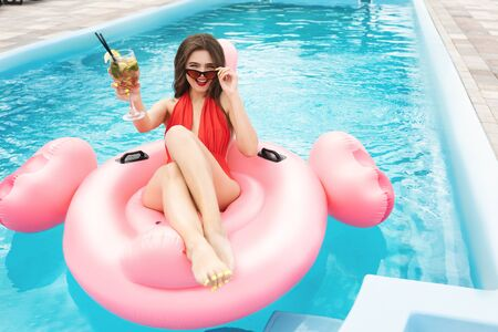 Photo for young beautiful brunette woman wearing red sexy swimsuit and sunglasses chilling in the pool having cocktail on inflatable flamingo looks attractive at resort - Royalty Free Image