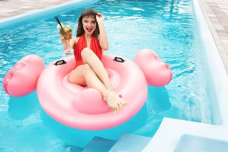Photo for young beautiful brunette woman wearing red sexy swimsuit and sunglasses chilling in the pool having cocktail on inflatable flamingo looks happy at resort - Royalty Free Image