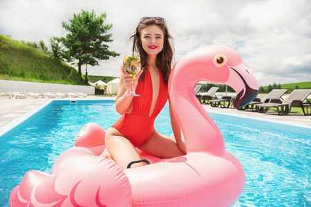 Photo for young brunette beautiful woman spending great time having fun at pool on pink flamingo drinking cocktail - Royalty Free Image