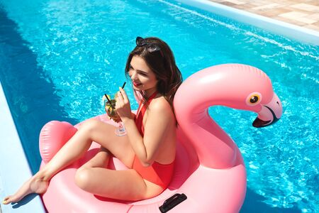 Photo for slim young attractive brunette woman with perfect body wearing red sexy swimsuit suntanning in the hotel pool drinking cocktail on holiday - Royalty Free Image