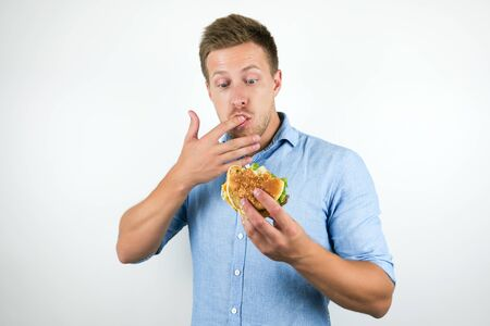 Photo for young handsome man enjoying cheeseburger from fast food restaurant licking his fingers while eating on isolated white background - Royalty Free Image