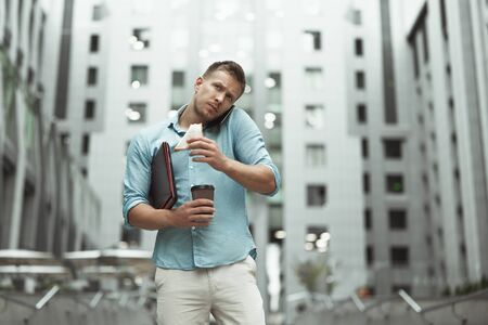 Foto de young handsome office worker talking on phone holding laptop and cup of coffee eating sandwich walking down the street near business center - Imagen libre de derechos