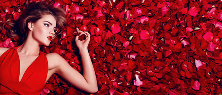 Photo pour Valentine's Day. Loving girl. The girl in a red dress lying on the floor in the petals of red roses. Background of red rose petals. Red lipstick on the lips from the beautiful girl. - image libre de droit