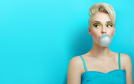Photo pour Fashionable girl with a stylish haircut inflates a chewing gum. The girl in the studio on a blue background. The girl's face with bright makeup and yellow with black shadows on the eyes. - image libre de droit