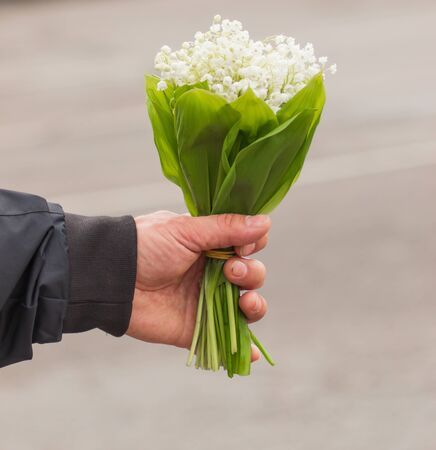 Photo pour bouquet of lily of the valley in hand - image libre de droit