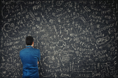 Foto de Rear view of a puzzled businessman in front of a huge blackboard try to solve hard mathematics calculation, formula and equations. Thinking of project ideas and business planning concept. - Imagen libre de derechos