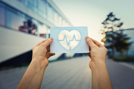 Foto de Close up of woman hands holding a paper sheet with the heart beating symbol inside, over hospital building background. - Imagen libre de derechos