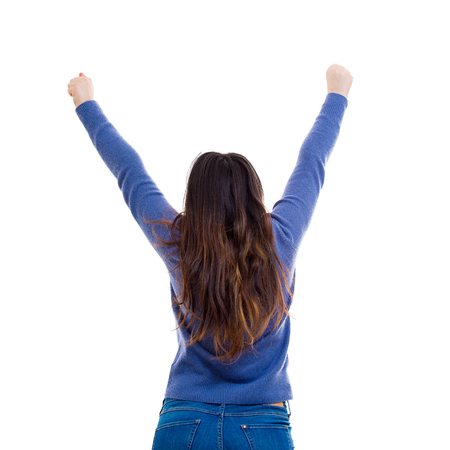 Foto de Freedom concept rear view of casual young woman student raising hands up wide opened celebrating success isolated over white background. - Imagen libre de derechos