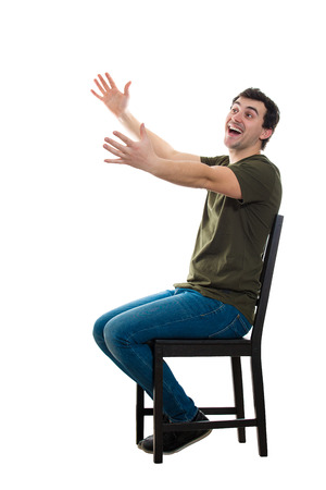 Foto de Side view full length portrait of excited casual young man seated on a chair keeps arms outstretched for hug like greeting an old friend isolated over white background with copy space. - Imagen libre de derechos