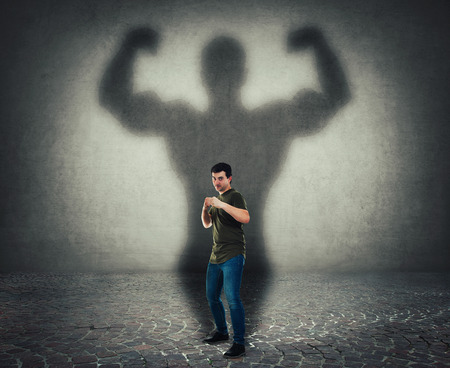 Foto de Confident man ready for battle stand in fighting position as a powerful hero, casting shadow of big strong muscular bodybuilder showing biceps. Self defense, inner strength and motivation concept. - Imagen libre de derechos