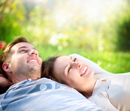 Photo pour Young Couple Lying on Grass Outdoor  - image libre de droit