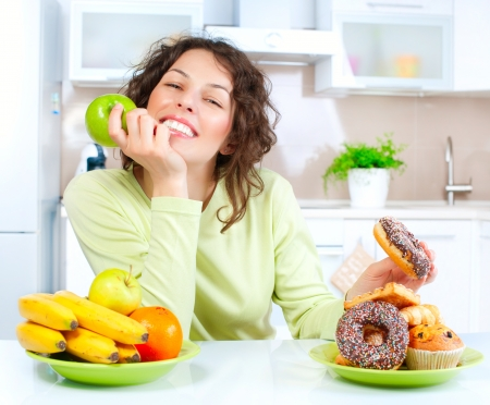 Photo for Diet  Beautiful Young Woman choosing between Fruits and Sweets  - Royalty Free Image