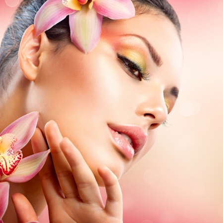 Photo for Beautiful Spa Girl With Orchid Flowers Touching her Face  - Royalty Free Image