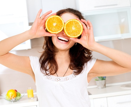 Photo pour Portrait of Young and Healthy Funny Woman with Orange over Eyes  - image libre de droit