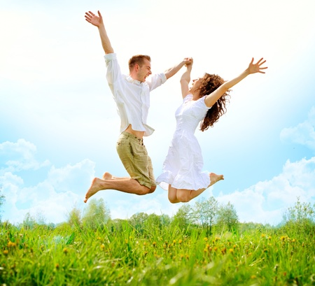 Photo pour Happy Couple Outdoor  Jumping Family on Green Field  - image libre de droit