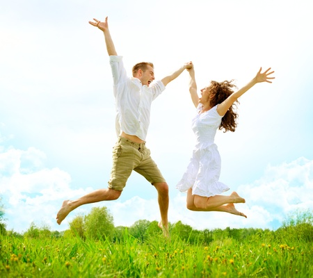 Photo for Happy Couple Outdoor  Jumping Family on Green Field - Royalty Free Image