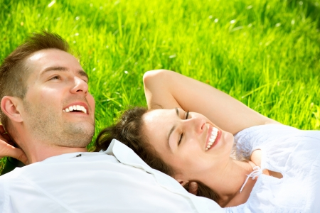 Foto de Young Couple Lying on Grass Outdoor  - Imagen libre de derechos