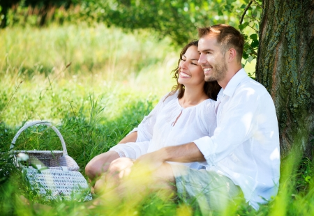 Photo pour  Young Couple Having Picnic in a Park  Happy Family Outdoor 	Young Couple Having Picnic in a Park  Happy Family Outdoor  - image libre de droit