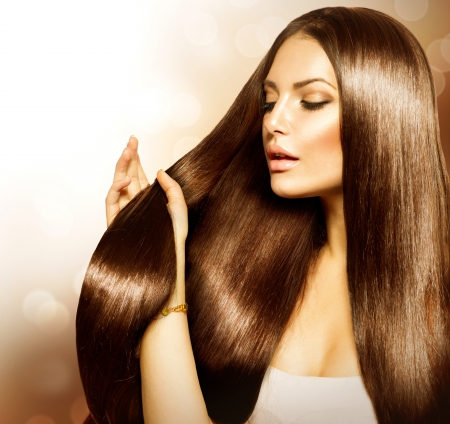Photo pour Beauty Woman touching her Long and Healthy Brown Hair  - image libre de droit