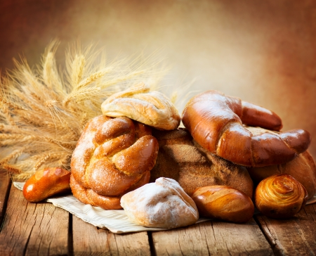 Photo for Bakery Bread on a Wooden Table  Various Bread and Sheaf  - Royalty Free Image