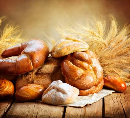 Foto de Bakery Bread on a Wooden Table  Various Bread and Sheaf  - Imagen libre de derechos
