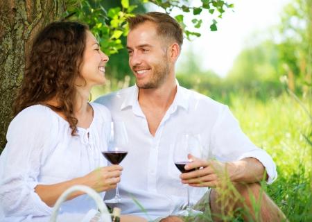 Foto de Picnic  Young Couple relaxing and drinking Wine in a Park  - Imagen libre de derechos
