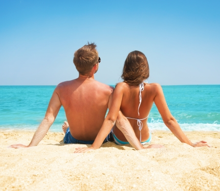 Young Couple Sitting together on the Beach  Vacation concept