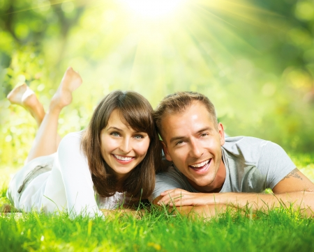 Foto de Happy Smiling Couple Together Relaxing on Green Grass Outdoor  - Imagen libre de derechos