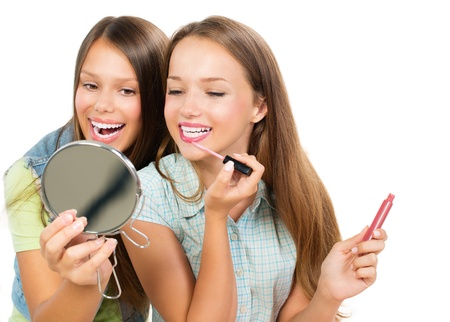 Photo pour Pretty Teenage Girls Applying Make up and Looking in the Mirror  - image libre de droit