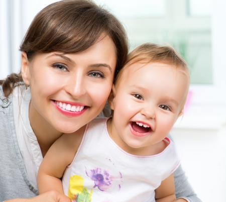 Photo pour Happy Smiling Mother and Baby kissing and hugging at Home  - image libre de droit