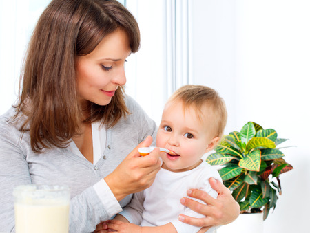 Photo pour Mother Feeding Her Baby Girl with a Spoon  - image libre de droit