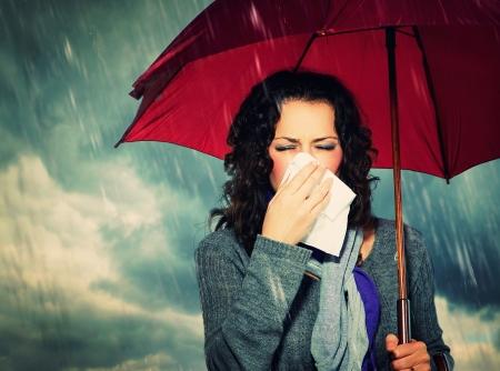Sneezing Woman with Umbrella over Autumn Rain Background