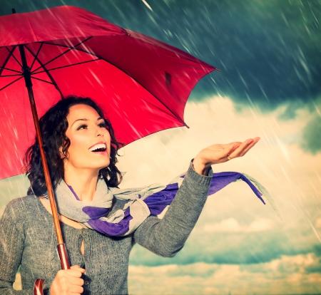 Smiling Woman with Umbrella over Autumn Rain Background