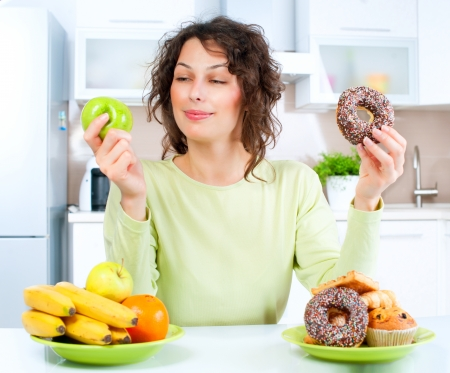 Foto de Dieting concept  Young Woman choosing between Fruits and Sweets  - Imagen libre de derechos