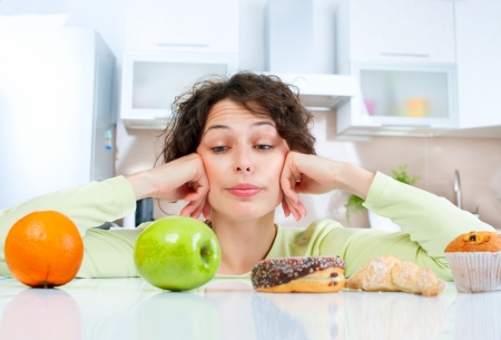 Photo for Dieting concept  Young Woman choosing between Fruits and Sweets  - Royalty Free Image