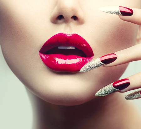 Photo pour Makeup and Manicure  Red Long Nails and Red Glossy Lips  - image libre de droit