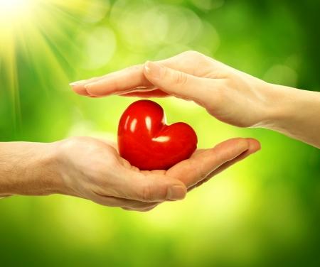 Foto de Valentine Heart in Man and Woman Hands over Nature Background - Imagen libre de derechos