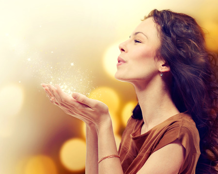 Photo pour Young Woman Blowing Magic Dust with Stars from her Hands  - image libre de droit