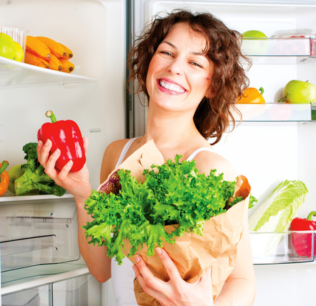 Photo pour Beautiful young woman near the refrigerator with healthy food  - image libre de droit