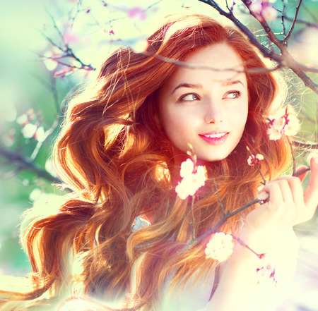 Photo for Spring beauty girl with long red blowing hair outdoors - Royalty Free Image