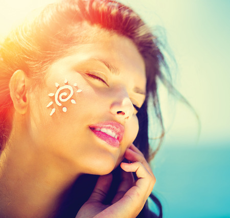 Photo for Beauty Girl Applying Sun Tan Cream on her Face  Sun Tanning - Royalty Free Image