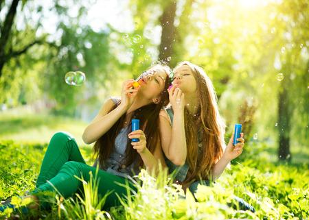 Foto de Joyful teenage girls laughing and blowing soap bubbles - Imagen libre de derechos