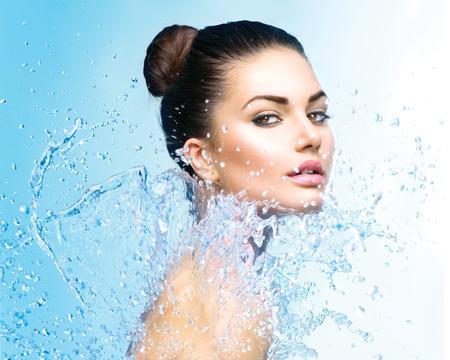 Photo pour Beautiful girl under splash of water over blue background - image libre de droit