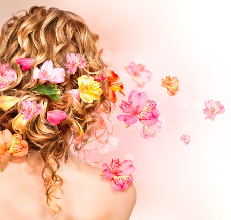Beautiful healthy curly hair decorated with flowers