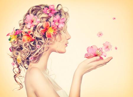Foto de Beauty girl takes beautiful flowers in her hands - Imagen libre de derechos