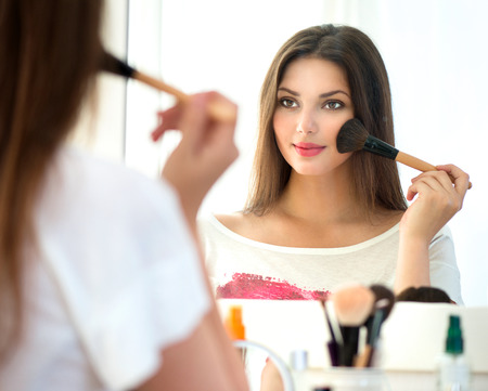Photo pour Beautiful girl looking in the mirror and applying makeup - image libre de droit